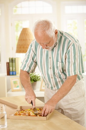 pizza cutter: Elderly man slicing up pizza, standing in living room. Stock Photo