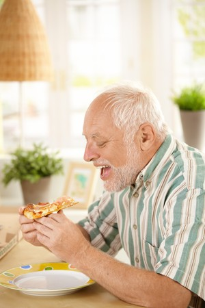 Hungry older man eating pizza slice, sitting at table at home. photo