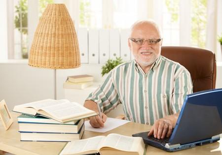 hombres haciendo ejercicio: Retrato de profesor senior sentado en la mesa de trabajo, haciendo un trabajo de investigación, equipo portátil, sonriendo a la cámara.