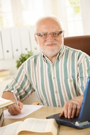 Senior professor working in his study, taking notes, using laptop computer, looking at camera. Stock Photo - 7899229