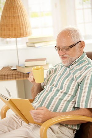 tea cosy: Elderly man reading book and having tea in armchair at home.