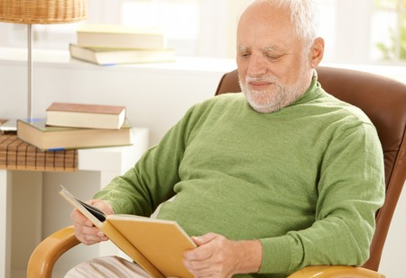 one mature man only: Old man sitting at home reading book in armchair.