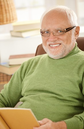 Portrait of smiling senior man wearing glasses, sitting at home holding book. photo