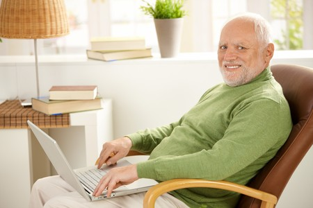 Portrait of aged man sitting in armchair with laptop computer, smiling at camera. photo