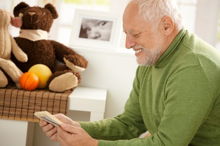 Happy grandfather looking at photo, smiling, sitting in children room. photo