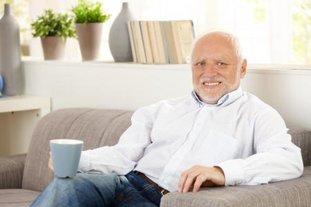 Smiling elderly man having coffee at home, sitting on sofa, looking at camera. photo