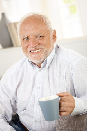 Portrait of smiling old man having coffee, looking happy. photo