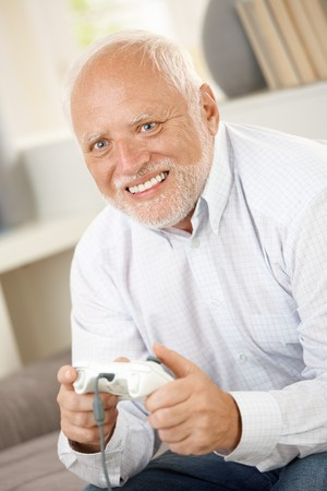 Older man having fun with computer game, smiling happily. Stock Photo - 7899198