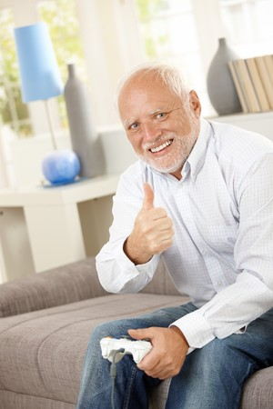 Older man sitting on couch giving thumb up while playing computer game, looking at camera, smiling. photo