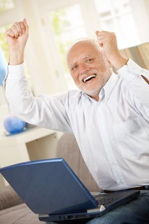 Viejo hombre celebrando en casa, riendo y levantar brazos, habiendo equipo portátil, mirando la cámara.
