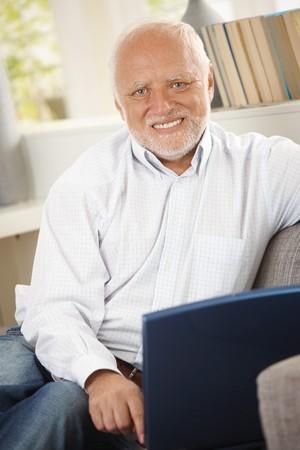 Portrait of smiling senior man using laptop computer, sitting at home, looking at camera. photo