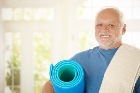 Portrait of sporty senior with polyfoam looking at camera, smiling photo