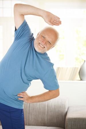 hombres haciendo ejercicio: Alegre senior haciendo ejercicios de deporte en la sala de estar, sonriendo a la cámara.