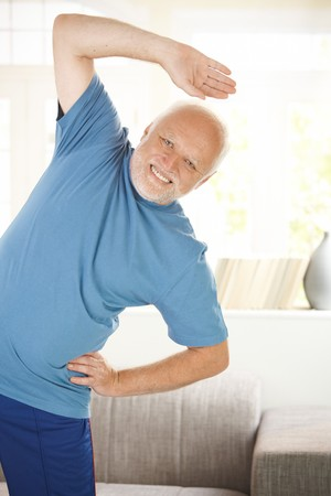 Cheerful senior doing sport exercises in living room, smiling at camera.