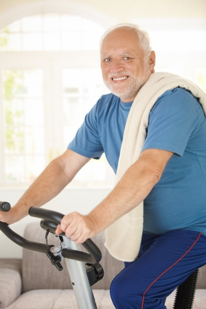 Active senior using exercise bike at home, smiling at camera. photo