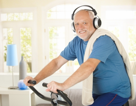 Active pensioner doing spinning on bike at home while listening to music, smiling at camera. photo