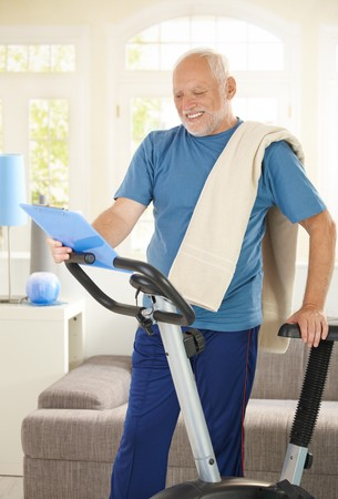 Active senior in sportswear with fitness equipment, looking at clipboard, smiling. photo