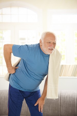 elderly pain: Senior man in sportswear having pain in back from exercises.