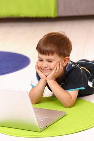 Niño feliz (5 años) acostado en el piso en el hogar utilizando equipo portátil.