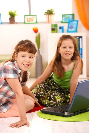 Elementary age girls sitting in living room with laptop computer, looking at camera, smiling. photo