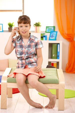 Cute girl using cellphone sitting at home, looking at camera, smiling. Stock Photo - 7899256