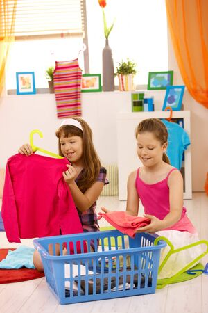 helping children: Young girls helping at home, packing clothes, smiling. Stock Photo