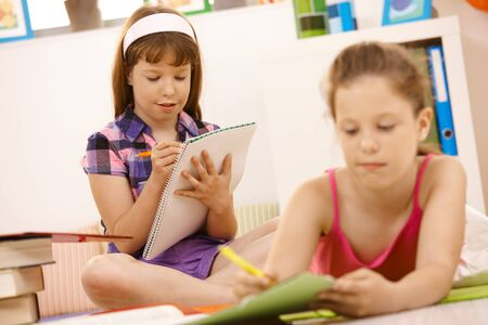 learning by doing: Schoolchildren writing into booklet at home, doing homework. Stock Photo