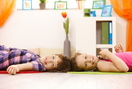 room mate: Portrait of young girls enjoying music via earphones, smiling at camera. Stock Photo