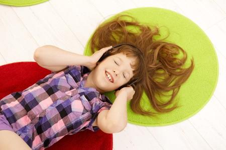Schoolgirl having fun listening to music with headphones eyes closed, smiling, lying on floor, overhead view. photo