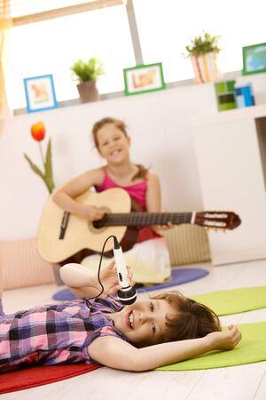 tocando musica: Retrato de colegialas tocando m�sica, uno cantando con micr�fono, otra tocando la guitarra, sonriendo.