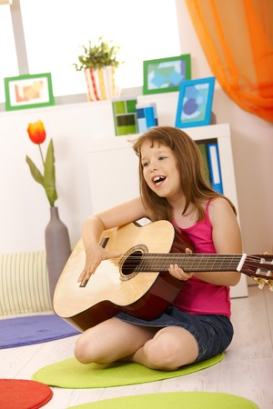 Portrait of schoolgirl with guitar, singing, sitting on living room floor. photo
