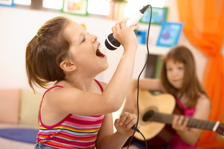 child singing: Young girl singing with microphone at home, concentrating, other girl playing guitar in background. Stock Photo