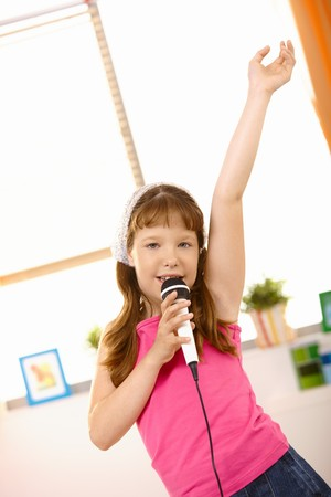 space age: Young girl singing into microphone with arm raised high, looking at camera.