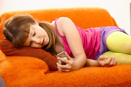 little girl child: Portrait of young girl looking at mobile phone, lying on sofa. Stock Photo