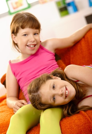 twin sister: Two young girls relaxing at home, smiling at camera on couch.