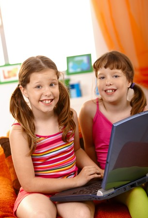 Happy schoolgirls enjoying browsing internet on laptop computer, with big toothy smile, looking at camera. Stock Photo - 7899244