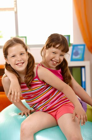 Small girls having fun with gym ball at home, laughing, looking at camera. Stock Photo - 7899242