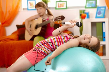 Young girl singing with microphone, posing on gym ball, smiling, friend playing guitar in background. photo