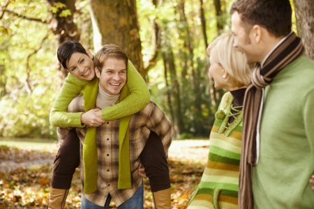 Outdoors portrait of happy young friends having fun in autumn park. photo