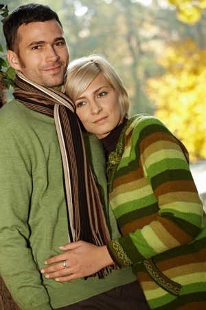 Portrait of happy young love couple in autumn park looking at camera, smiling. Stock Photo - 7899690