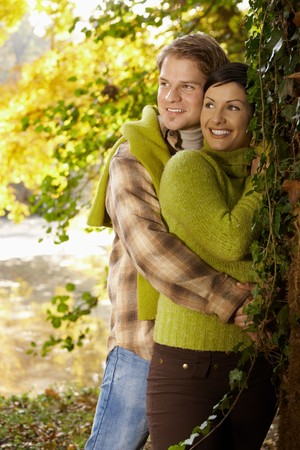 Portrait of happy young couple in autumn park standing at tree, laughing. photo
