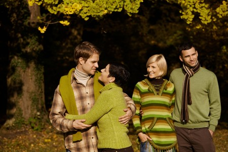 Happy young couples standing in autumn park, smiling. photo