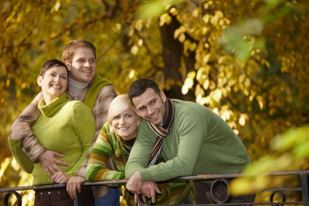 Portrait of happy young friends standing in autumn park, leaning to railing, smiling. photo