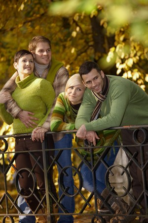Two smiling couples on autumn walk in park. photo