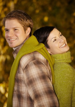 Portrait of happy, smiling couple standing back to back in autumn park. photo