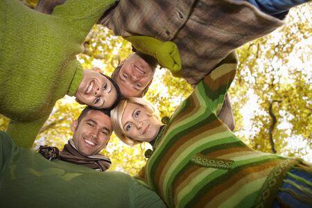 low angle views: Amigos felices de pie con sus cabezas juntos en oto�o de bosque, sonriendo. Vista de �ngulo bajo.  Foto de archivo