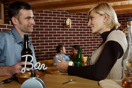 Man and woman chatting in bar, smiling at each other, young couple in background. photo
