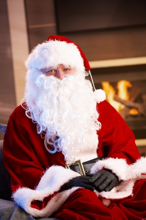 Indoor portrait of Santa Claus sitting by fireplace, looking at camera. photo