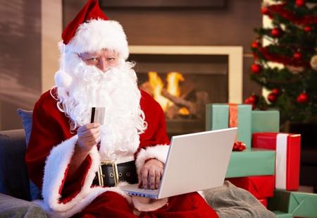 papa noel: Santa Claus utilizando equipo de compras de Navidad se presenta en internet pagando con tarjeta de cr�dito.  Foto de archivo