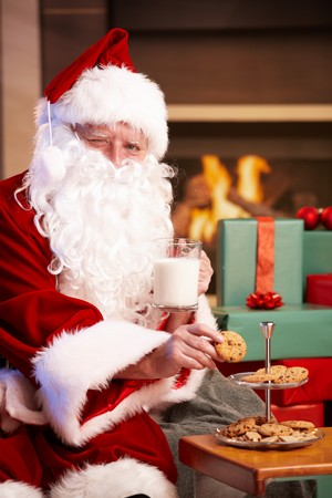 Happy Santa Claus sitting at fireplace drinking milk eating chocolate chip cookies, looking at camera, winking photo